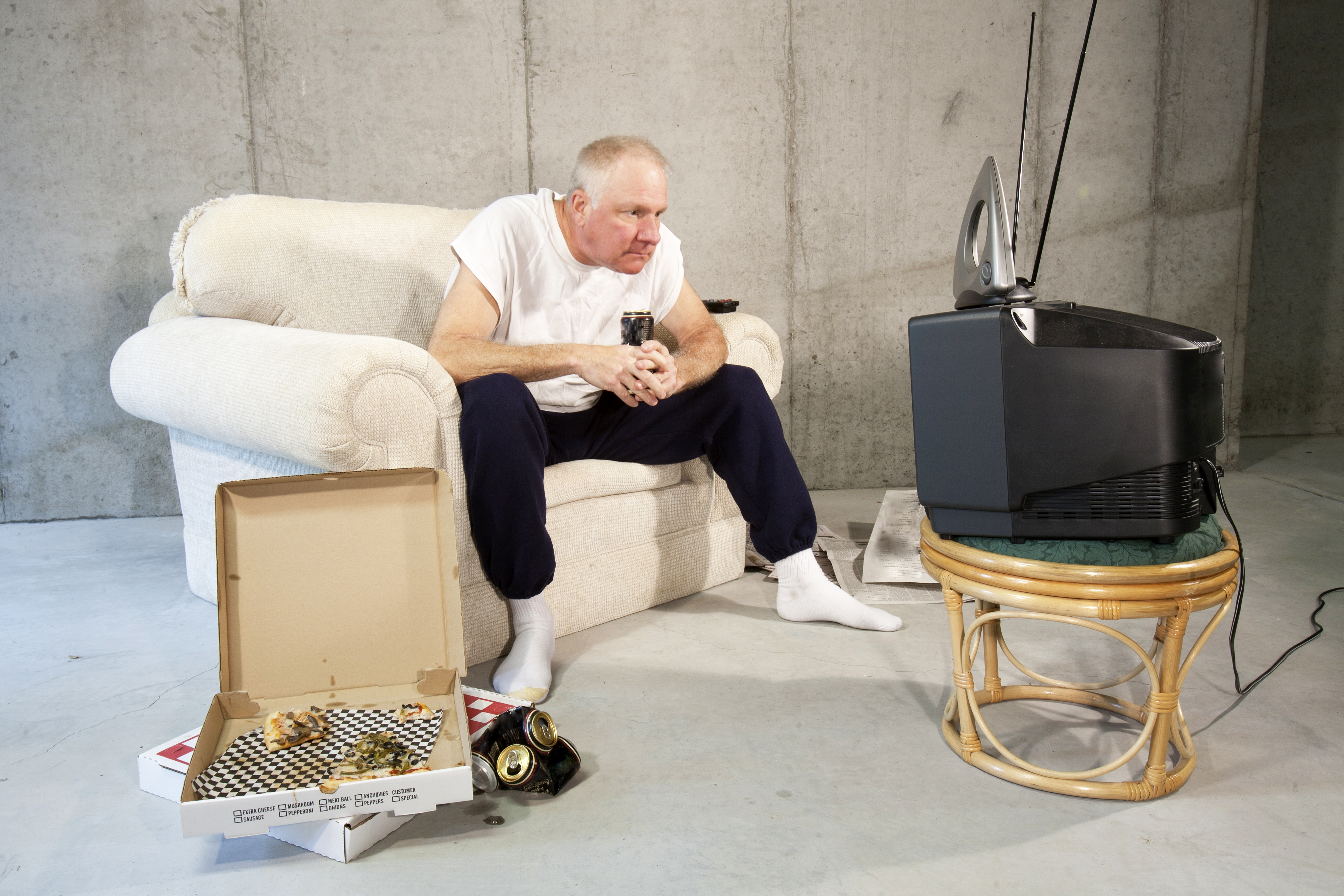 Man dressed in sweatpants and t-shirt watching a tv with rapt attention